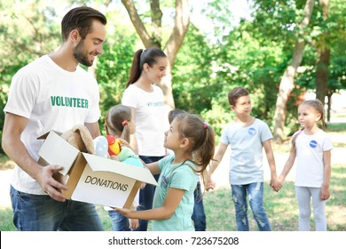 Young volunteers and children with box of donations outdoors