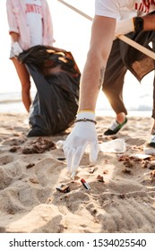 Young volunteers couple cleaning beach from rubbish, picking up batteries