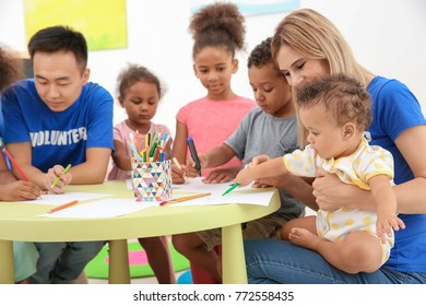 Young volunteers drawing with little children at table. Volunteering abroad concept