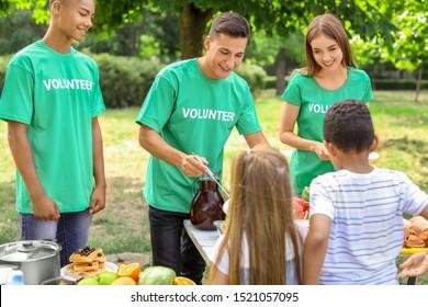 Young volunteers giving food to poor children outdoors