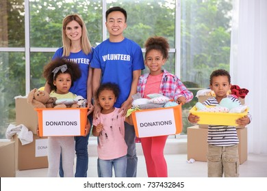 Young volunteers and little children with donations boxes in light room. Volunteering abroad concept