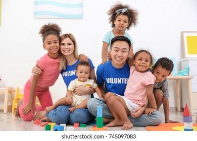 Young volunteers with little children in light room. Volunteering abroad concept