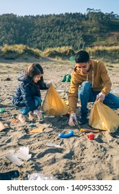 Young volunteers picking up trash on the beach