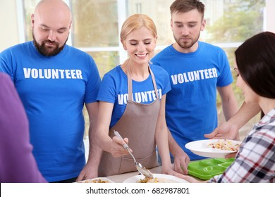 Young volunteers serving food to homeless people