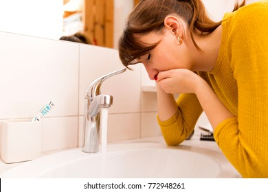 Young vomiting woman near sink in bathroom
