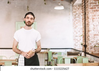 Young waiter in black cap,white t-shirt and apron standing with notepad in hands and dreamily looking in camera while working in cafe