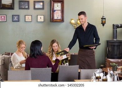 Young waiter giving menu to female customers at restaurant