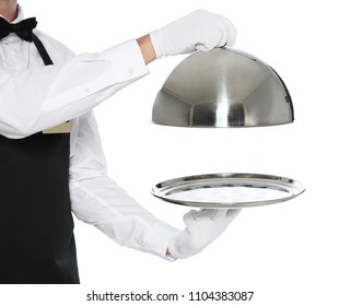 Young waiter holding metal tray with lid on white background