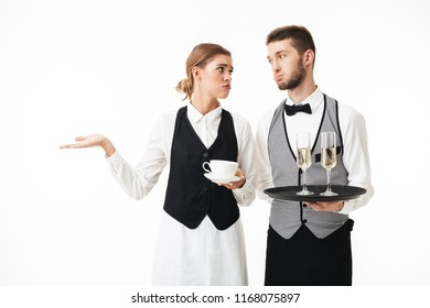 Young waiter holding tray with glasses of champagne and sad waitress holding cup of coffee in hands tiredly looking at each other over white background