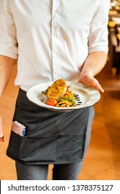 young waiter with plate full of tasty dish