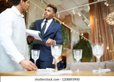 Young waiter setting the table for the banquet controlled by the manager at the restaurant
