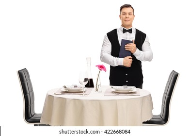 Young waiter standing next to a restaurant table and holding a menu isolated on white background