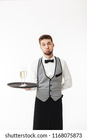 Young waiter in uniform holding tray with glasses of champagne tiredly looking in camera over white background