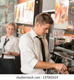 Young waiter and waitress working in bar serving coffee