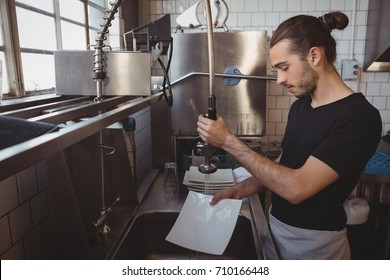 Young waiter washing plates while standing in cafe