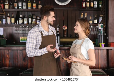 Young waiters with notebook in restaurant