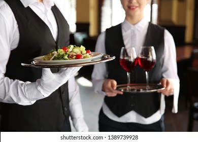 Young waiters with salad and wine in restaurant
