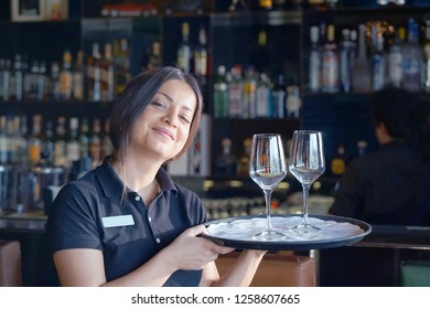 A young waitress carries wine glasses on a tray to the client of the hotel restaurant. Shelves with bottles of alcohol in the background. The concept of service.