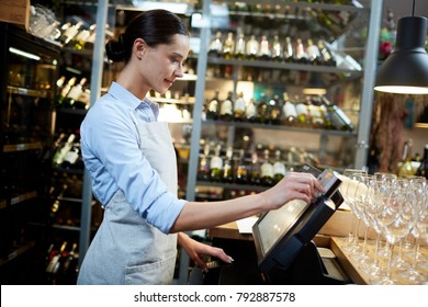 Young waitress or cashier registrating new orders of clients in computer