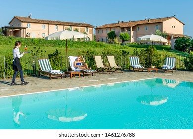 Young waitress serves a poolside cocktail to a customer sitting on a lounger in a resort in the countryside of Pisa, Tuscany, Italy