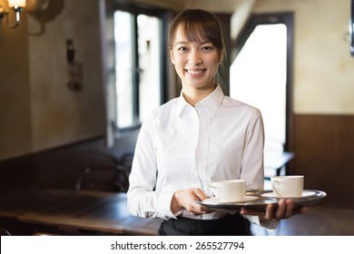 young waitress serving coffee at cafe