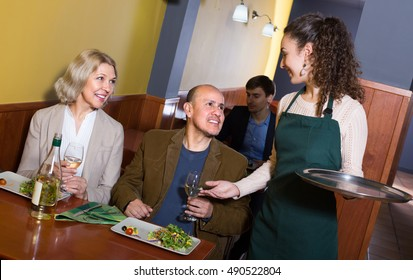 Young waitress serving smiling mature couple at dinner in cafe