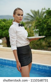 Young waitress with tray and drink posing by the swimming pool