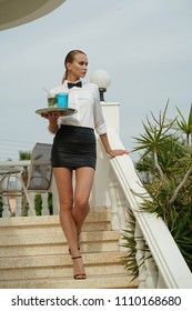 Young waitress with tray and drinks on the stairs