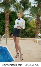 Young waitress with tray and drinks standing by the swimming pool