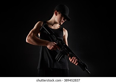 Young wan in with rifle in hands on black background poses for the camera/Young wan with gun on black background