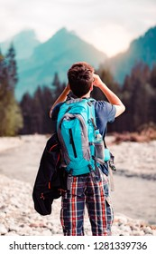 Young wanderer with backpack looks through a binoculars on mountains peaks, stands over a river. Boy spends a vacation in mountains, wandering with backpack, he is wearing sports summer clothes