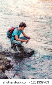 Young wanderer takes pure water from a river into mug. He is sitting on a rock over the river, rests during a hike, spends a vacation on wandering with backpack, he is wearing sport summer clothes