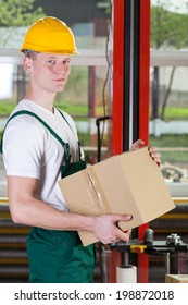 Young warehouse worker in green overalls holding box