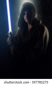 Young warrior holding a lightsaber over a dark background