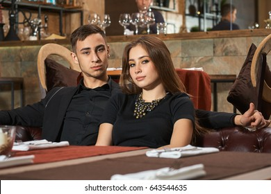 Young wealthy beautiful couple sitting in a restaurant. Going to have nice dinner.