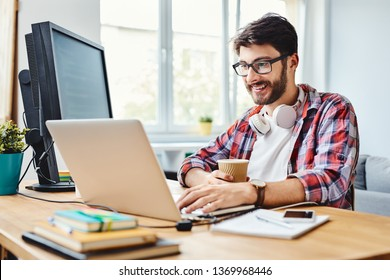 Young web designer working on code and drinking coffee in his home office