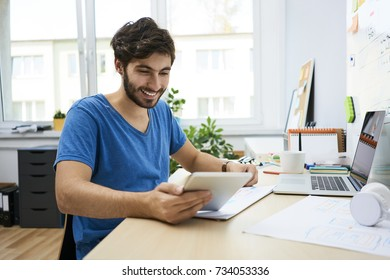 Young web designer working with websiste wireframe and tablet in home office