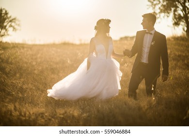 Young wedding couple enjoying romantic moments outside on a summer meadow. Happy groom and bride walking on summer sunset meadow