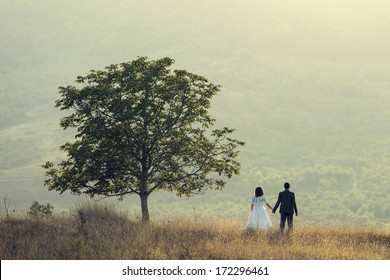 Young wedding couple holding near a tree