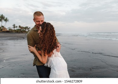 Young wedding couple hugging and having fun on black sand beach. Happy couple laughing together walking on beach holidays. Vacation concept of two adult people holding hands on black sand beach