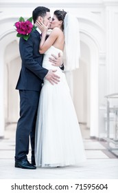 Young wedding couple kissing. Bright white colors.