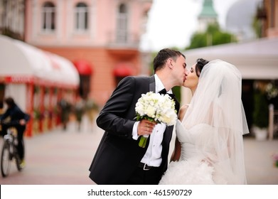 Young wedding couple kissing at street, groom and bride holding hands, walking street