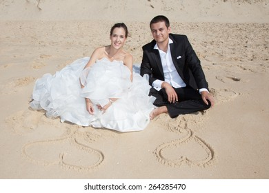 Young wedding couple painting heart on beach sand