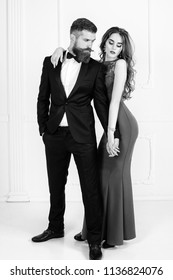 Young wedding couple of sexy girl with brunette hair and pretty face in red bride dress and handsome man in black groom suit. Couple in black suit and red dress, rich bearded man and fashion woman