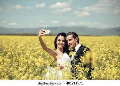 young wedding couple of sexy girl with pretty face in white bride dress holds mobile phone and handsome man in black groom suit in field with yellow flowers on natural background with blue sky