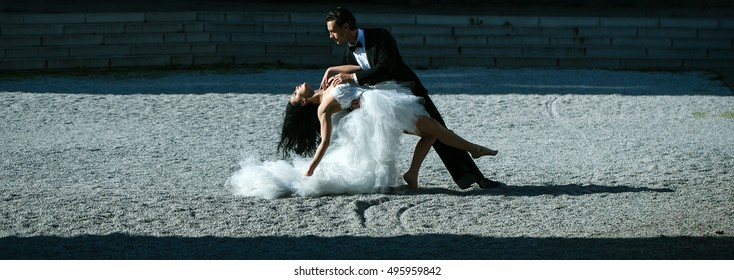 young wedding couple of sexy girl with brunette hair and pretty face in white bride dress and handsome man in black groom suit standing dancing on ground sunny outdoor