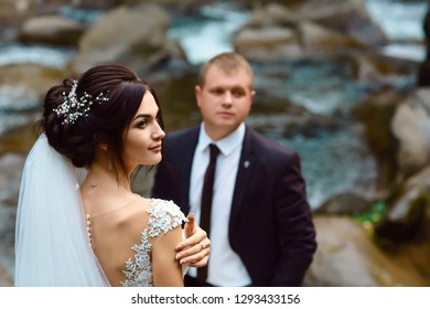 young wedding couple of sexy pretty girl or woman with hair in white bride dress and handsome man near beautiful grand waterfall in mountain