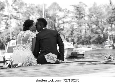 Young wedding couple sitting at a wooden dock and kissing