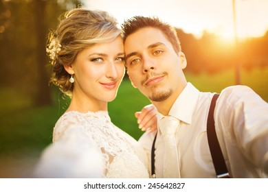 Young wedding couple taking a selfie of themselves as they enjoy romantic moments outside on a summer meadow