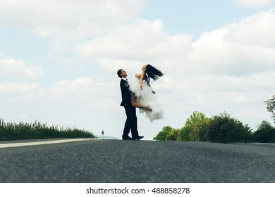 young wedding happy couple of sexy girl with brunette hair and pretty face in white bride dress and handsome man in black groom suit dancing on road way on cloudy blue sky nature background